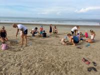 Barnklubben har storsamling på stranden och bygger sandslott.