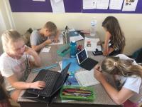 Skolarbete i klassrum Sura Thani dator samt penna och papper