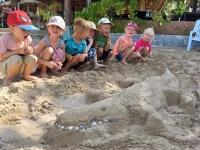 Lek på stranden, där barnklubben skapar en krokodil.